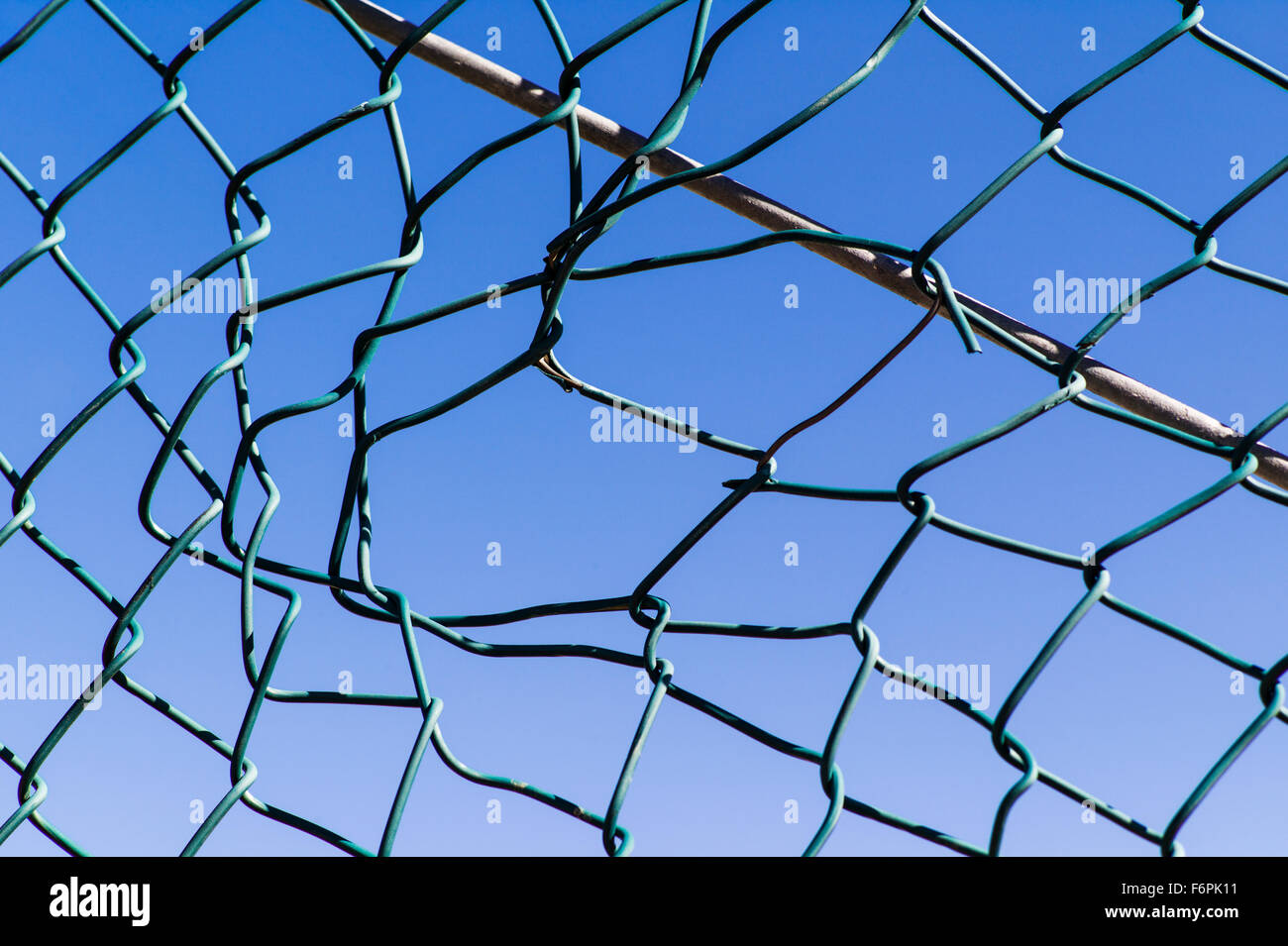 Zerrissenes Loch in einem Drahtgeflecht, Hurrikan oder Zyklon Stahl Zaun Stockbild