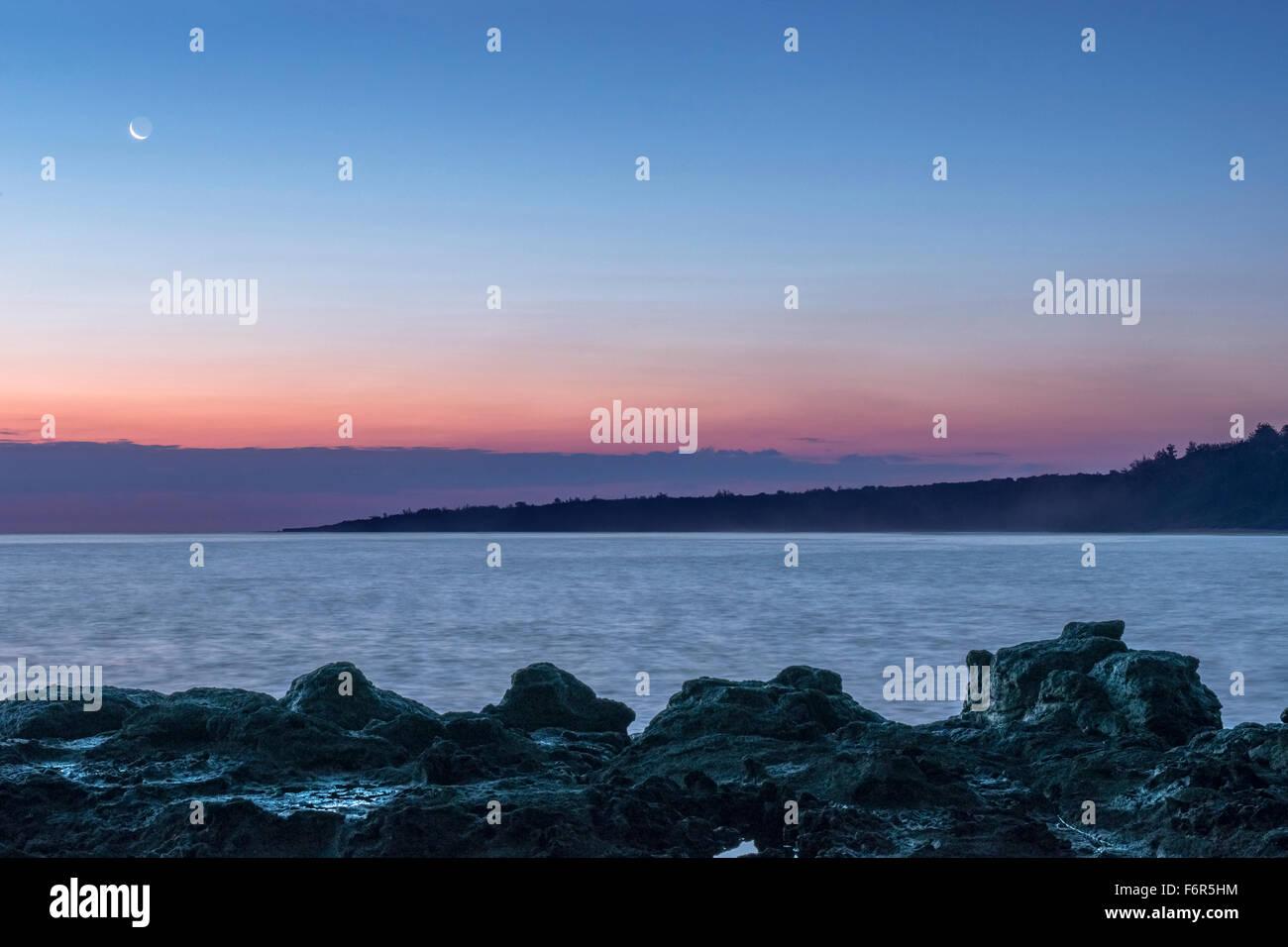 Sonnenaufgang über Felsformationen am Strand Stockfoto