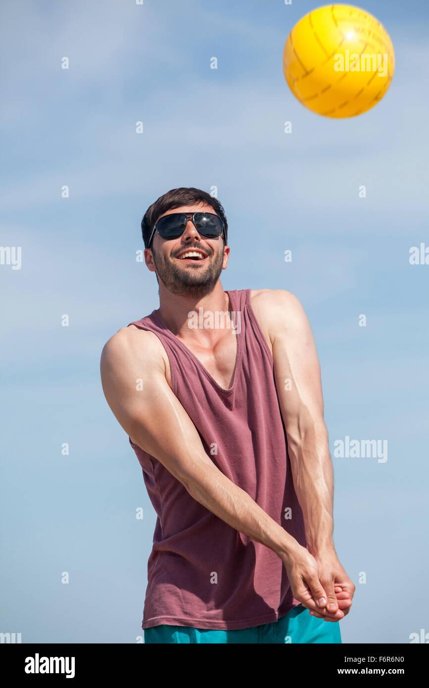 Junger Mann spielen Beach-volleyball Stockbild
