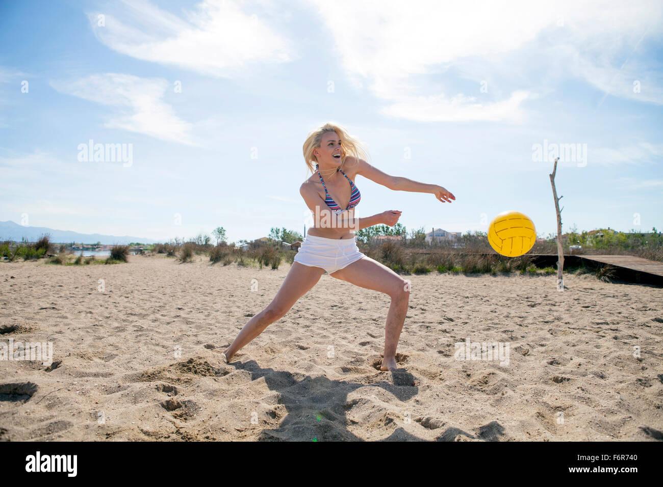 Junge Frau spielen Beach-volleyball Stockbild