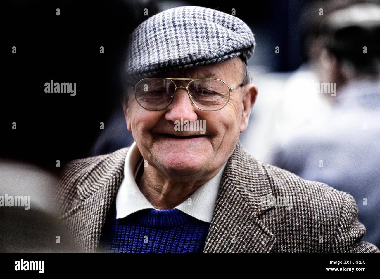 Ein Lächeln auf den Lippen alte Herr ein Tweed Tuch Mütze und Jacke Stockbild