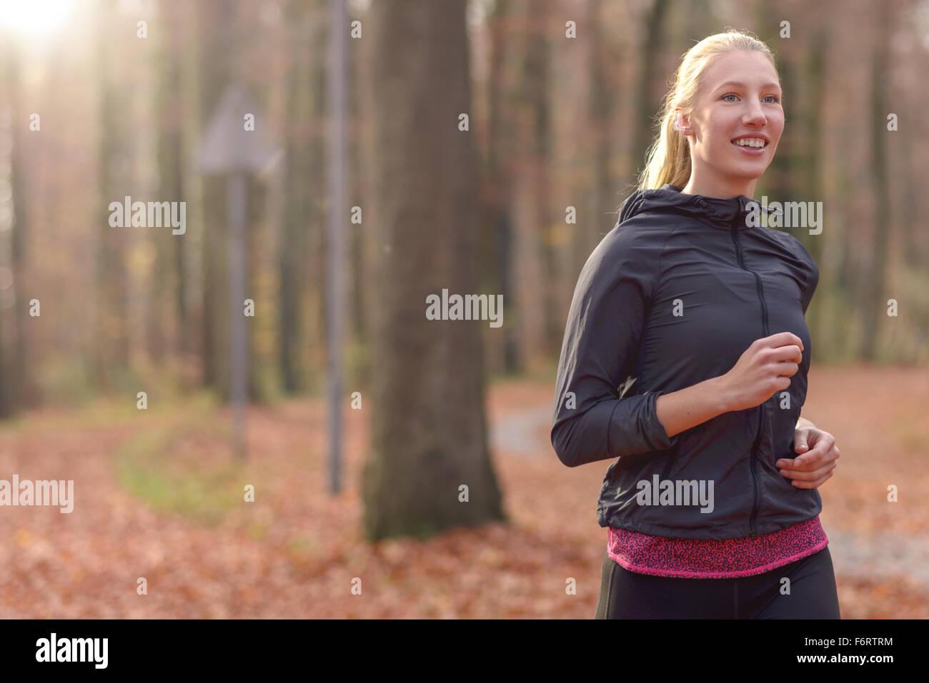 Ziemlich junge Frau, die durch Herbst Joggen fit oder Wald nähert sich die Kamera fallen, Oberkörper Porträt Stockbild