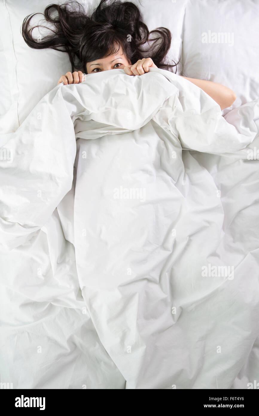 Gemischte Rassen Frau herausschauen von Bettdecken Stockfoto