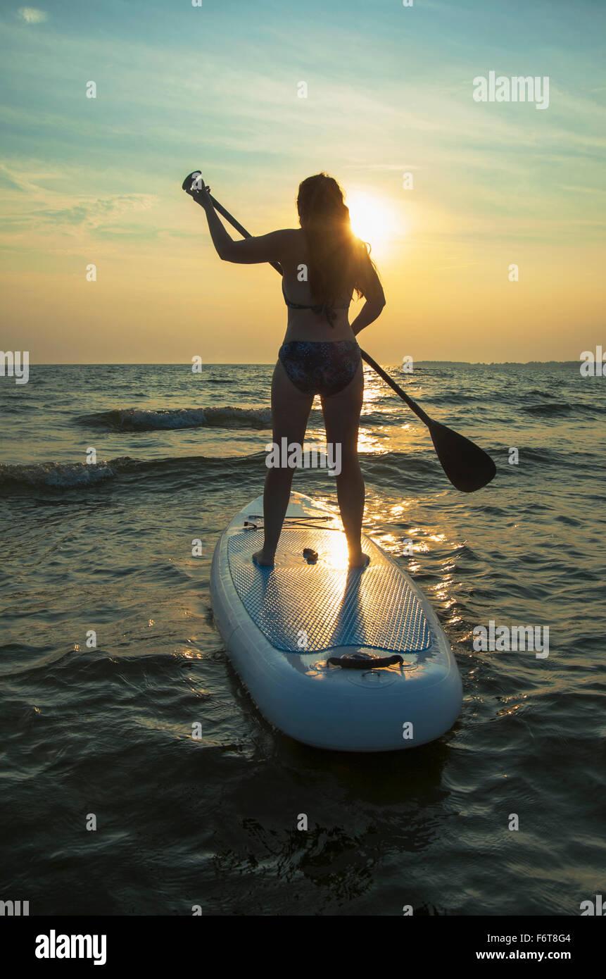 Frau stehend auf Paddleboard in See Stockfoto