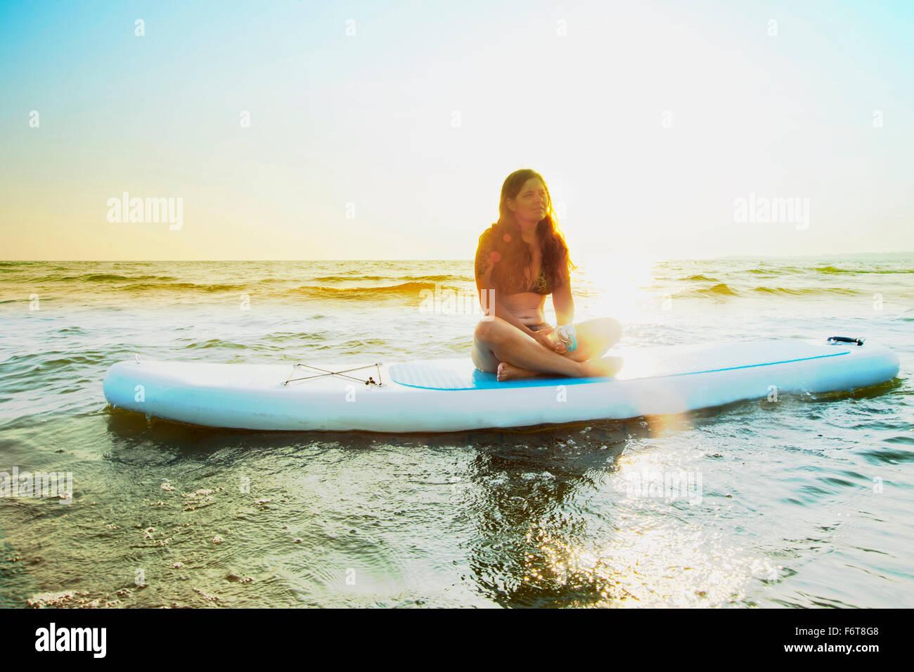 Frau sitzt auf Paddleboard in See Stockbild