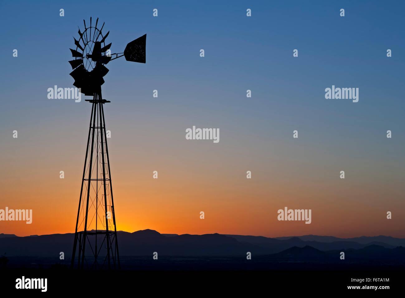 Windmühle Silhouette gegen orangefarbenen Himmel, Organ Mountains in der Nähe von Las Cruces, New Mexico, Stockbild