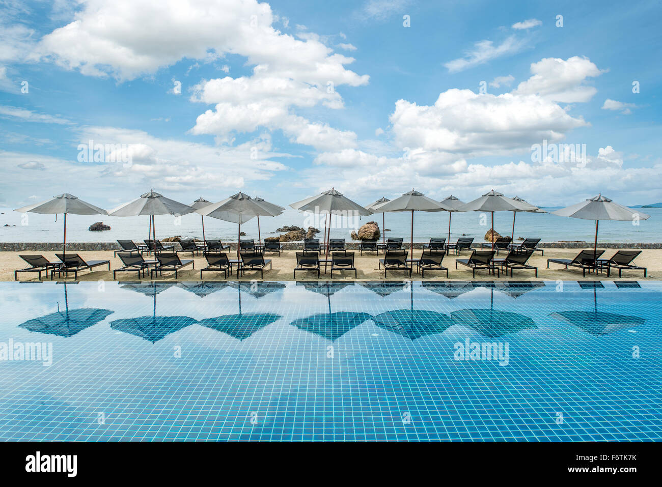 Sommer, Reisen, Urlaub und Ferien-Konzept - Tropical Beachresort mit Liegestühlen und Sonnenschirmen in Phuket, Stockbild