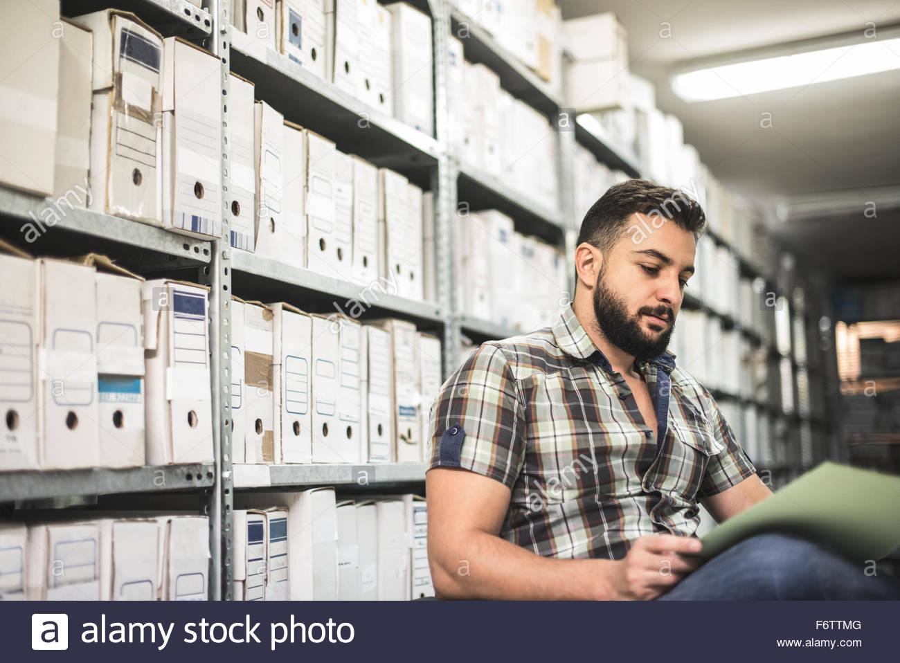 Bärtiger Mann arbeitet auf Datei in einem Archiv Stockbild