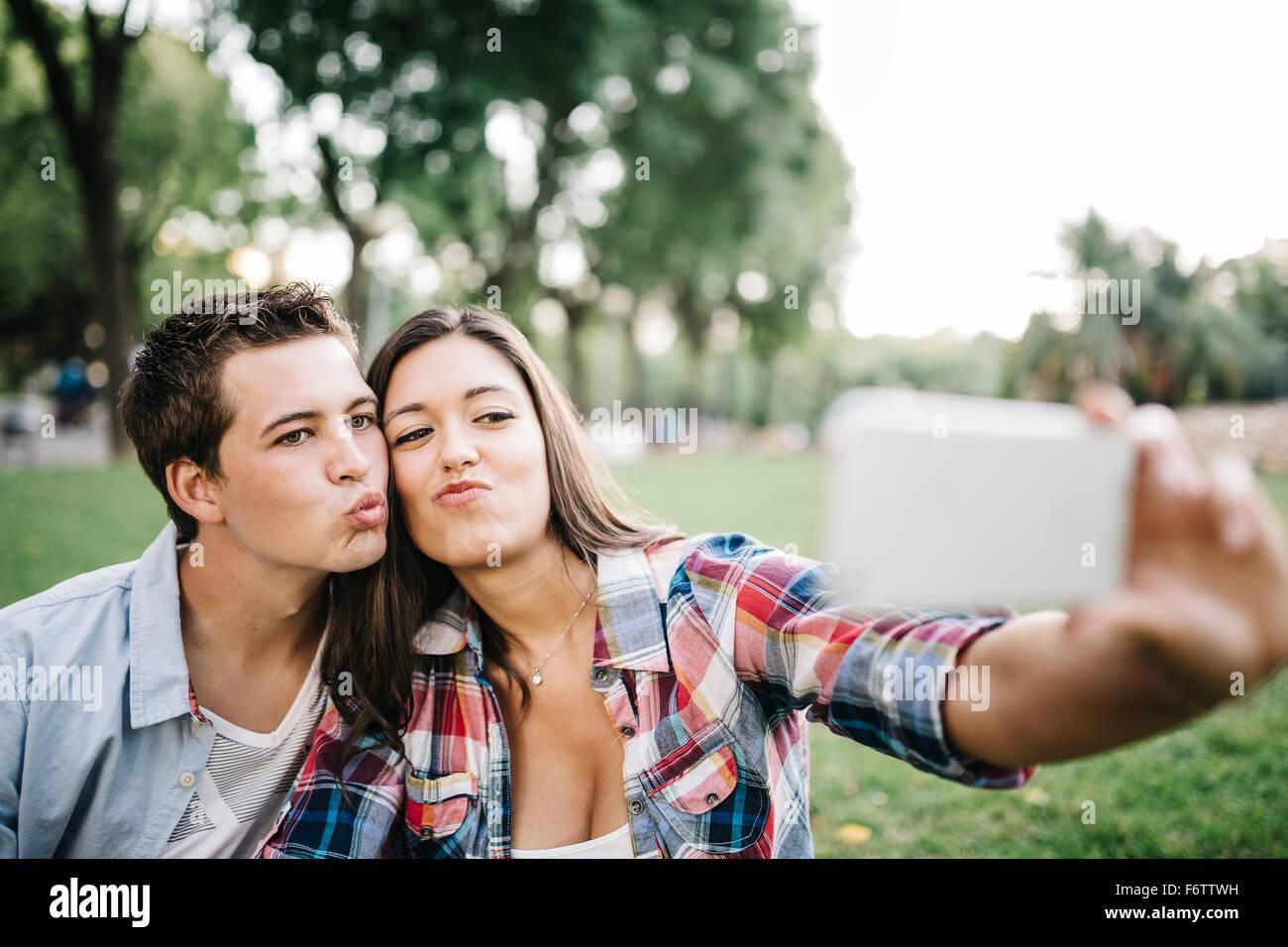 Porträt des jungen Paares in der Liebe nehmen ein Selbstporträt mit Smartphone in einem park Stockbild