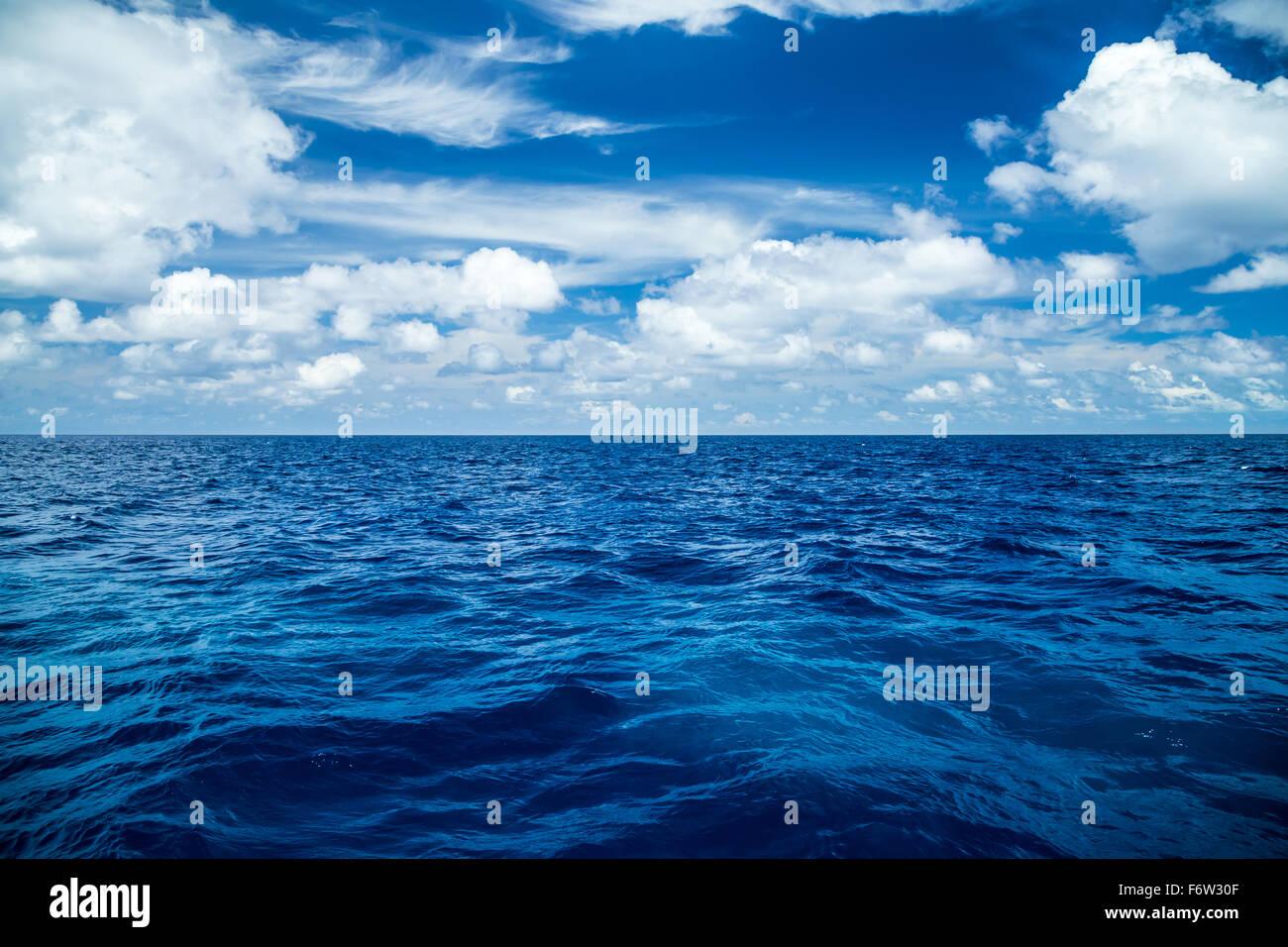 Blick auf den tiefblauen Ozean vor blauen Wolkenhimmel Stockbild