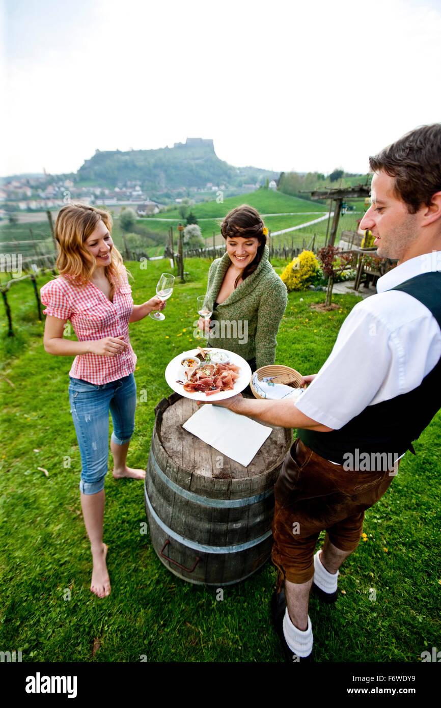 Zwei junge Frauen genießen Sie lokale Spezialitäten in einem Weinberg, Riegersburg, Steiermark, Österreich Stockbild