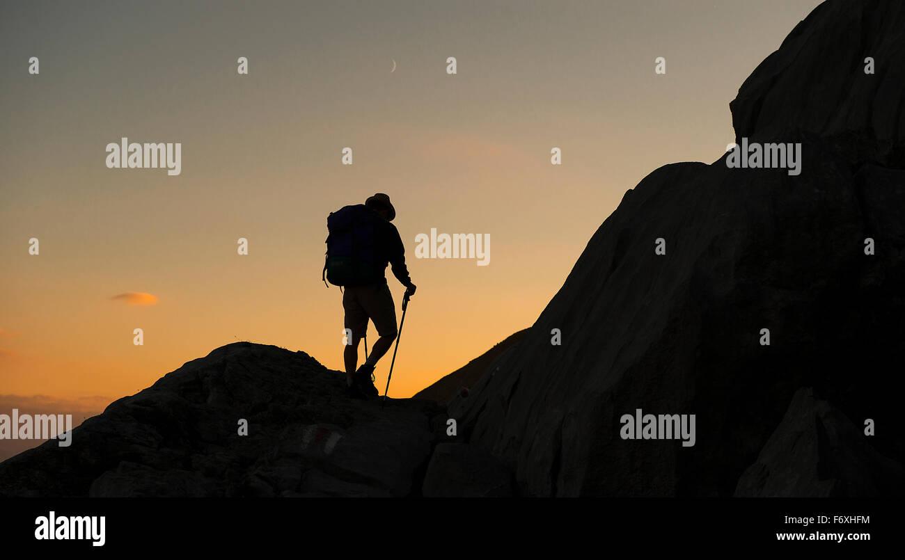 Ein einsamer Wanderer auf Mt Santis in den Schweizer Alpen beginnt seinen Abstieg, wie die Sonne über der nahe Stockbild