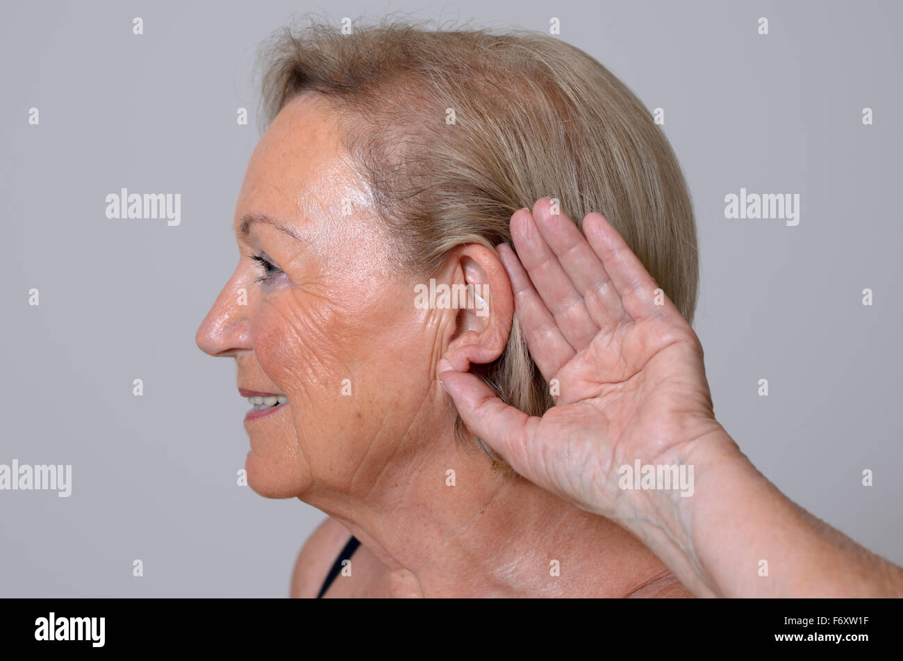 Ältere Dame mit Hörproblemen durch Alterung, hielt ihre Hand zu ihrem Ohr wie sie kämpft, um zu hören, Stockbild
