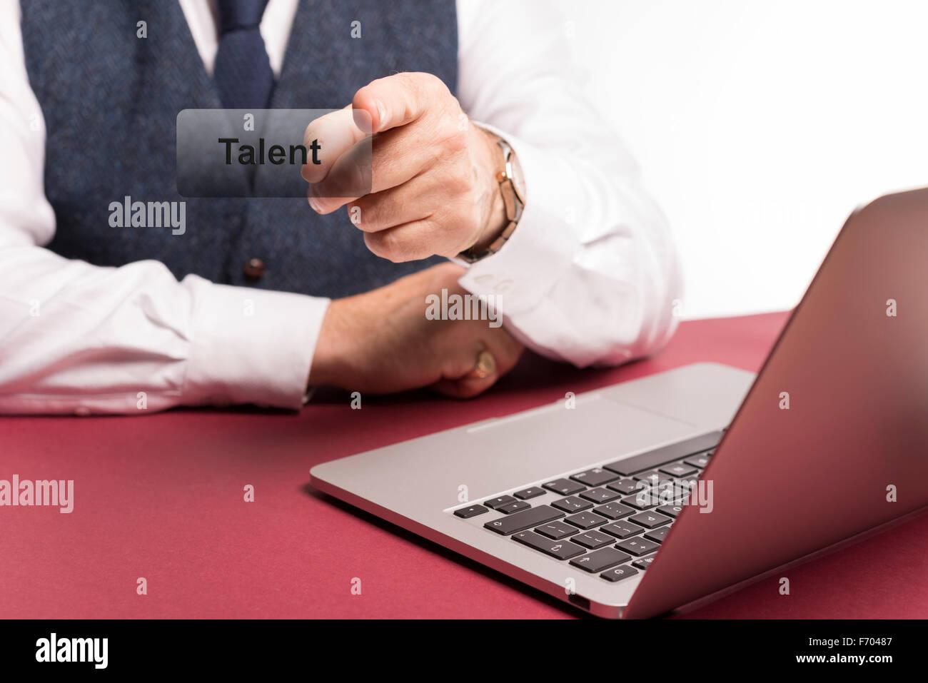 Elegant gekleidet Geschäftsmann sitzt am Schreibtisch mit Laptop im Hinblick auf das Wort Talent auf einem Stockbild