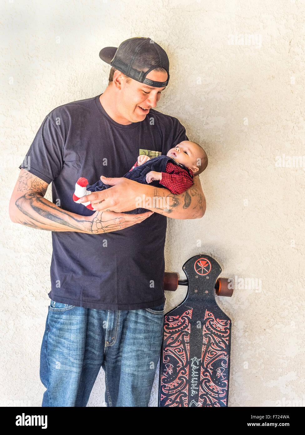 Tausendjährige Vater Skateboarding mit Tattoos halten sein kleiner Sohn 2 1/2 Monat und steht neben der Papa Skateboard. Stockfoto