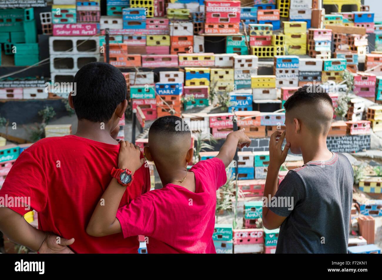 RIO DE JANEIRO, Brasilien - 16. Oktober 2015: Junge Brasilianer stehen und blicken auf eine soziale Kunst-Installation Stockbild