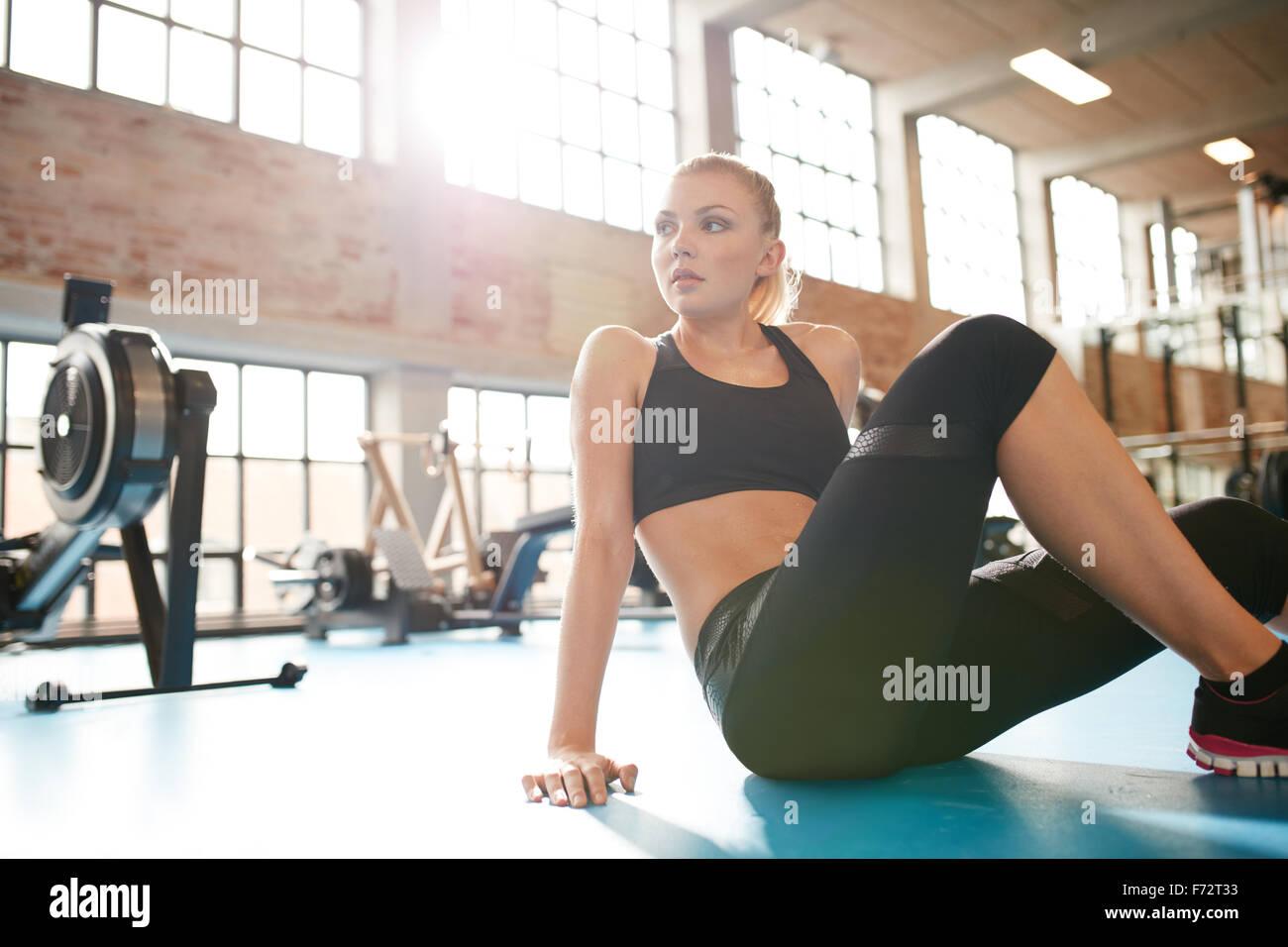 Innenaufnahme einer jungen Frau, die einen Bruch in der Turnhalle. Fitness Frauen sitzen auf dem Boden wegsehen. Stockbild