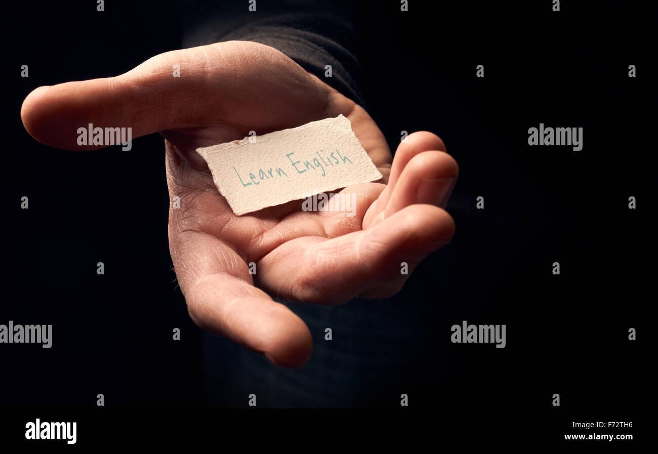 Ein Mann hält eine Karte mit eine handschriftliche Nachricht drauf, Englisch lernen. Stockbild