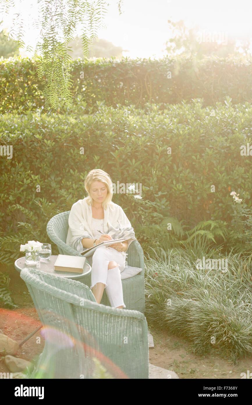 Blonde Frau sitzt in einem Korbstuhl in einem Garten. Stockbild