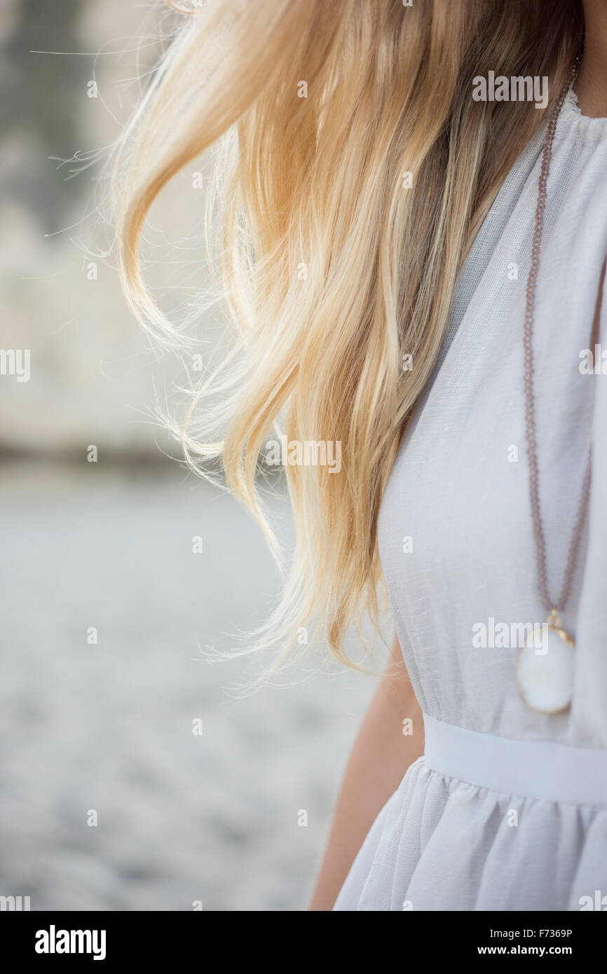 Blonde Frau trägt ein Kleid und Halskette an einem Sandstrand. Stockbild