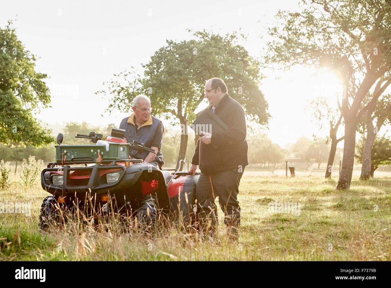 Zwei Männer, ein Bauer und ein Mann mit einem Klemmbrett, durch ein Quadbike in einem Obstgarten. Stockfoto