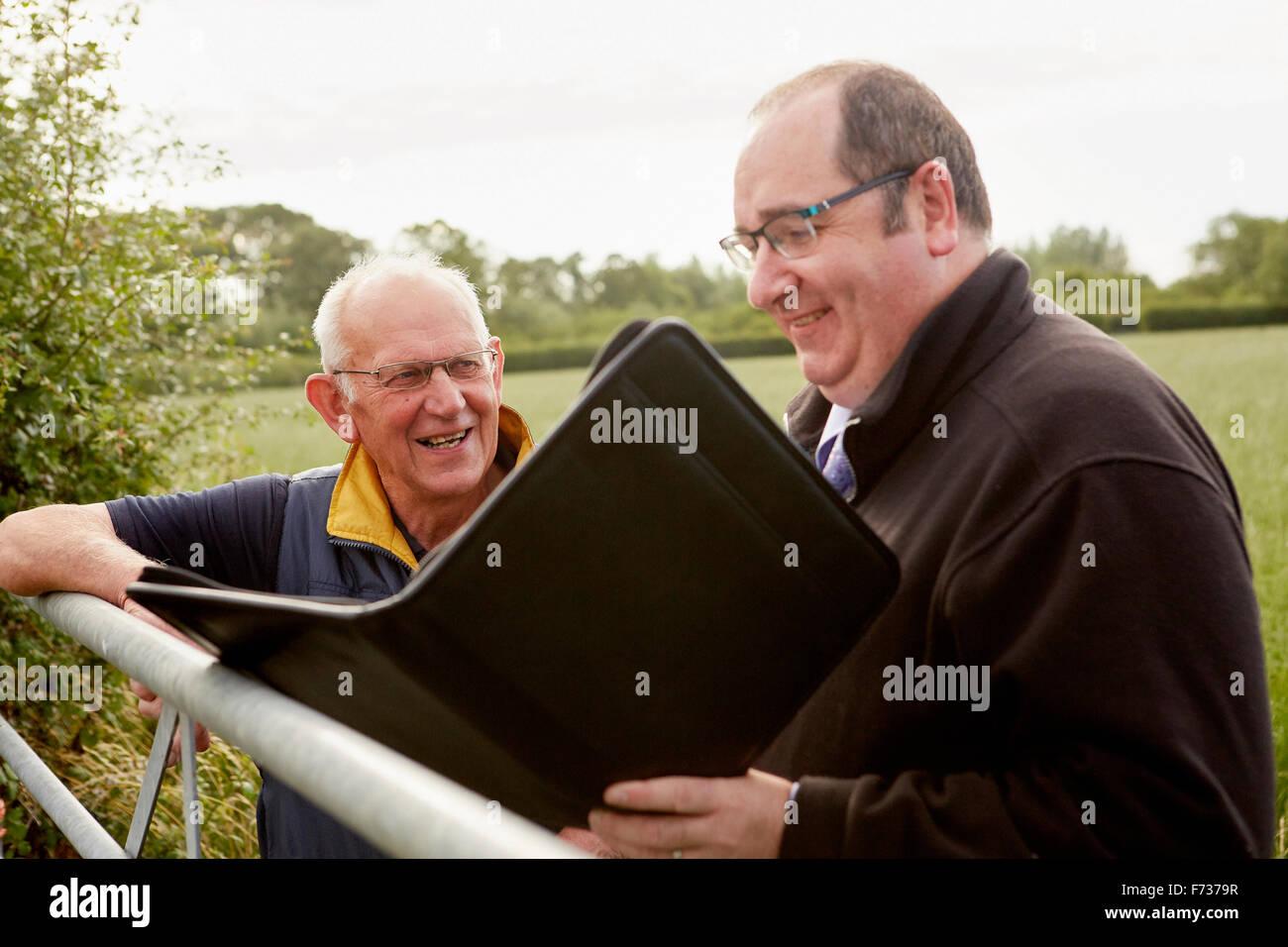 Zwei Männer stehen mit Blick auf einen Hof, eine mit einer geöffneten Datei und Papierkram. Stockbild