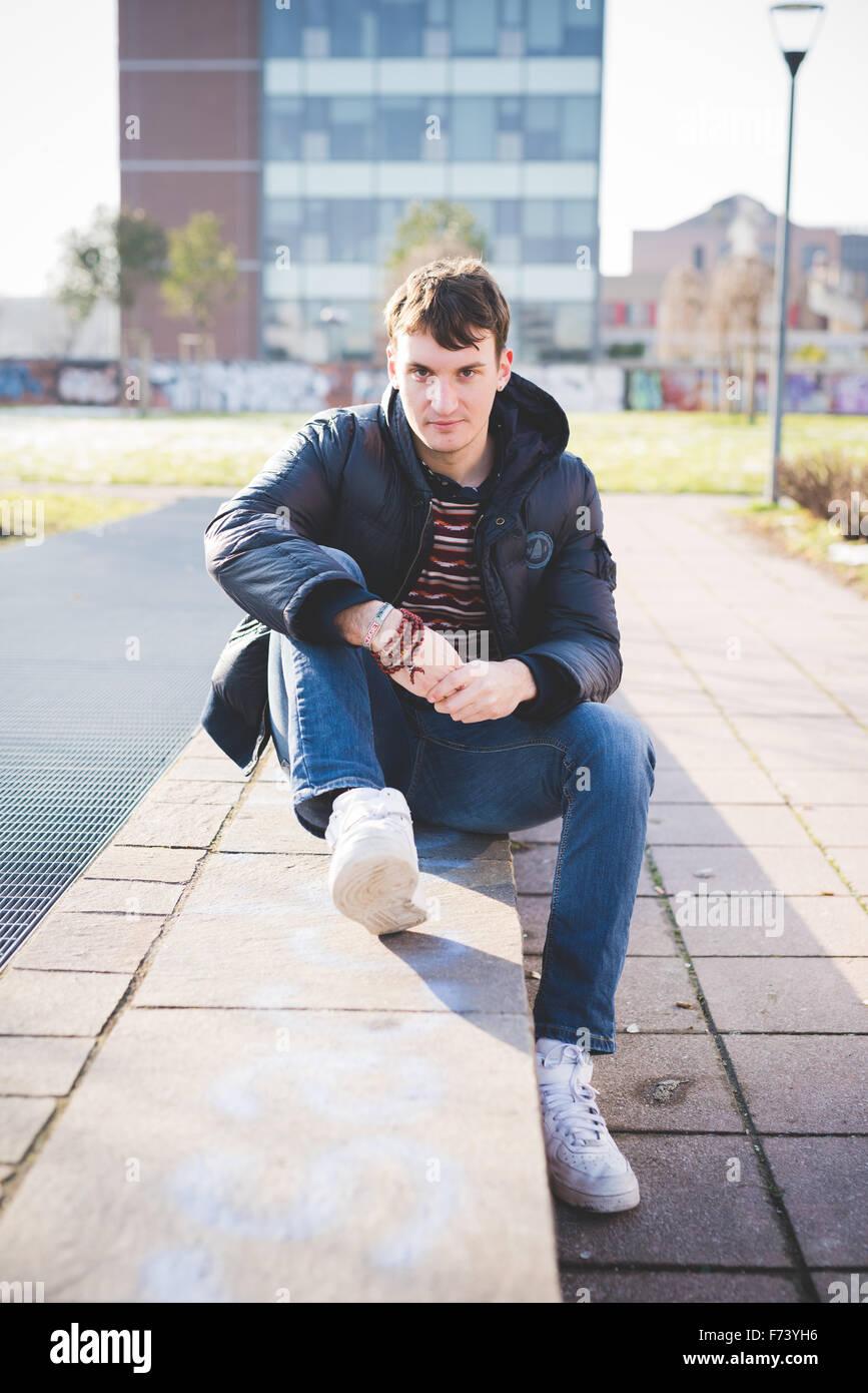 junge hübsche kaukasischen braune Haare Mann sitzt auf einer kleinen Mauer, auf der Suche in der Kamera, lächelnd Stockbild