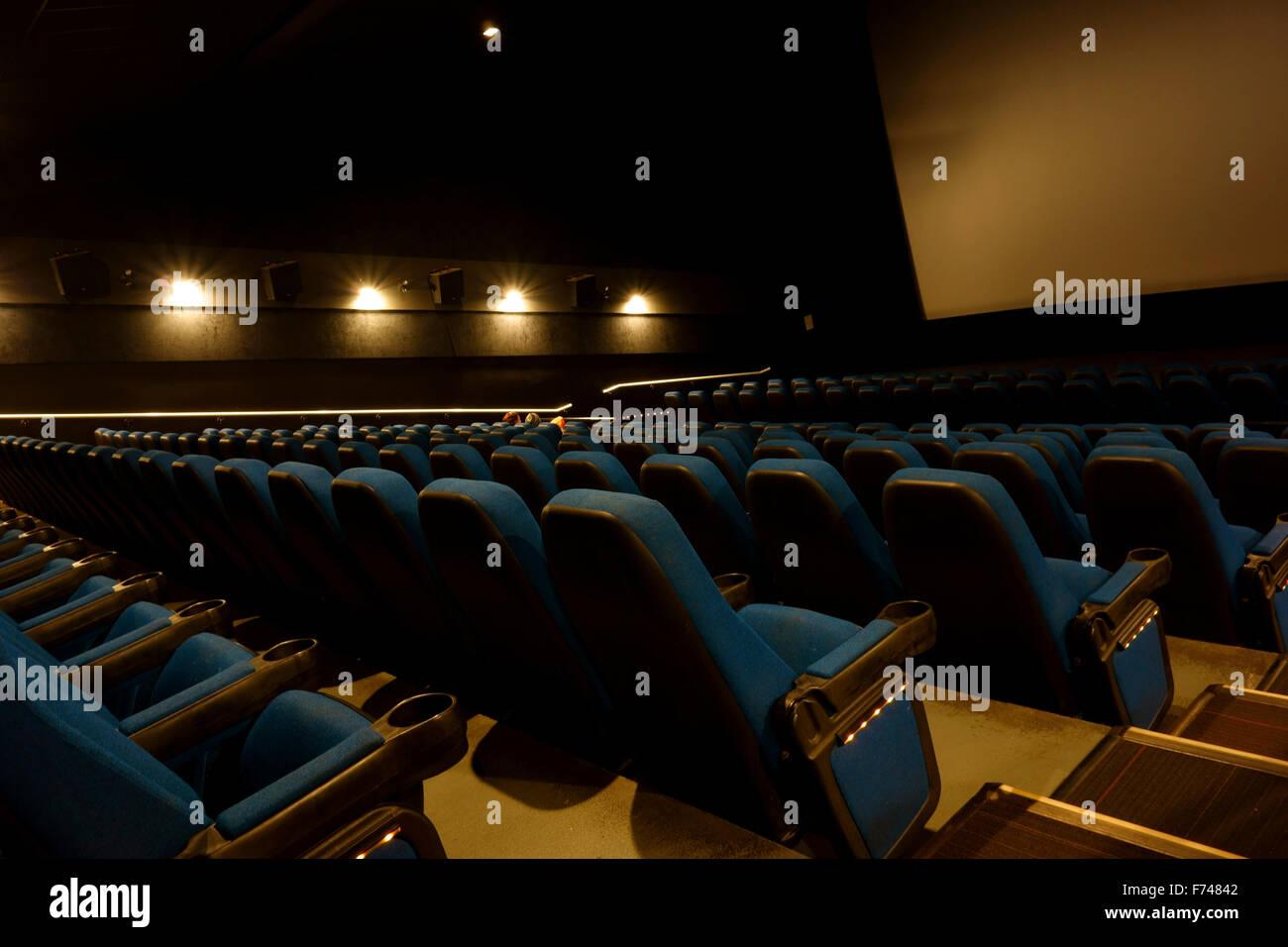 Sitzplätzen und die Leinwand in einem Kino oder Kino mit Licht gedimmt und niemand Stockfoto