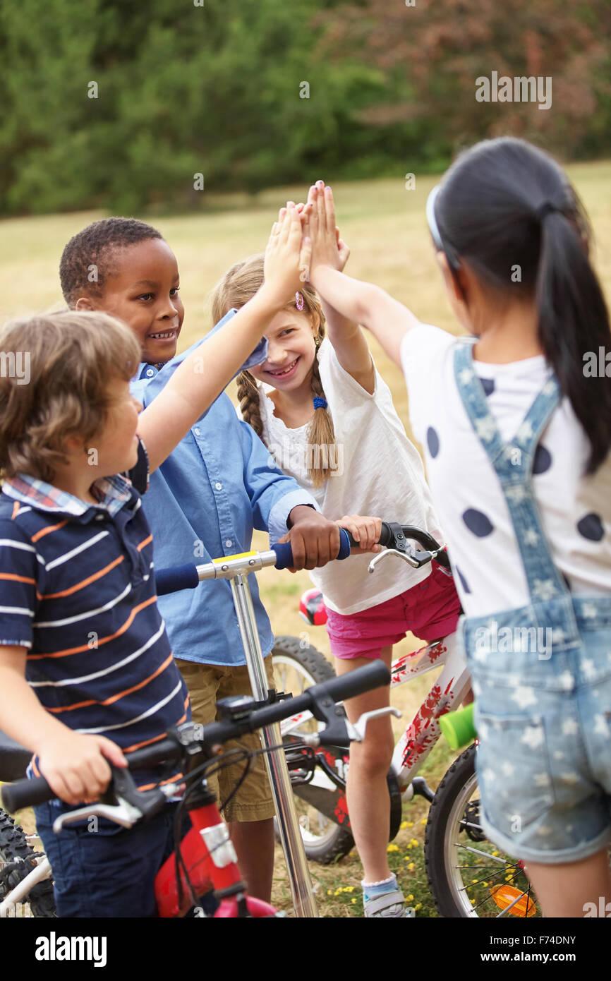 Kinder mit hohen fünf Geste in einem interracial team Stockbild