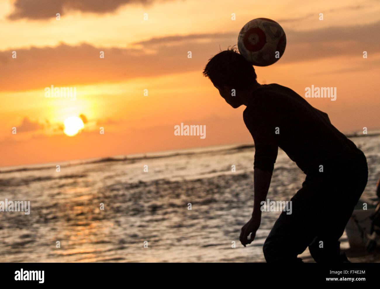 Fußball-Spieler leitet ein Ball am Strand bei Sonnenuntergang, Zihuatanejo, Guerrero, Mexiko. Stockbild