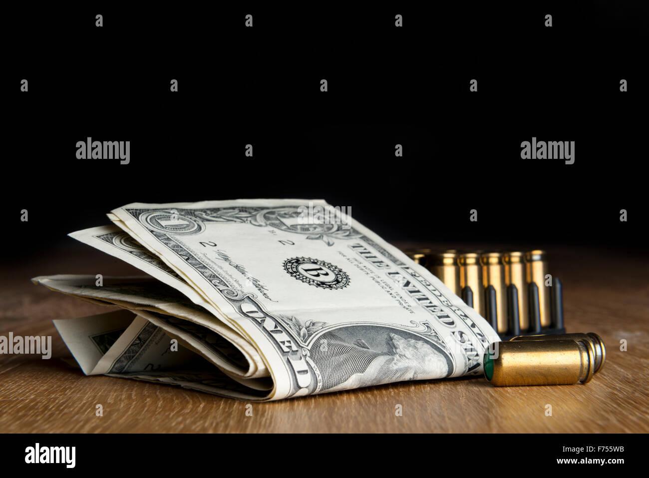 Bild von Dollarnoten mit Pistolen Patronen auf einem Tisch Stockbild