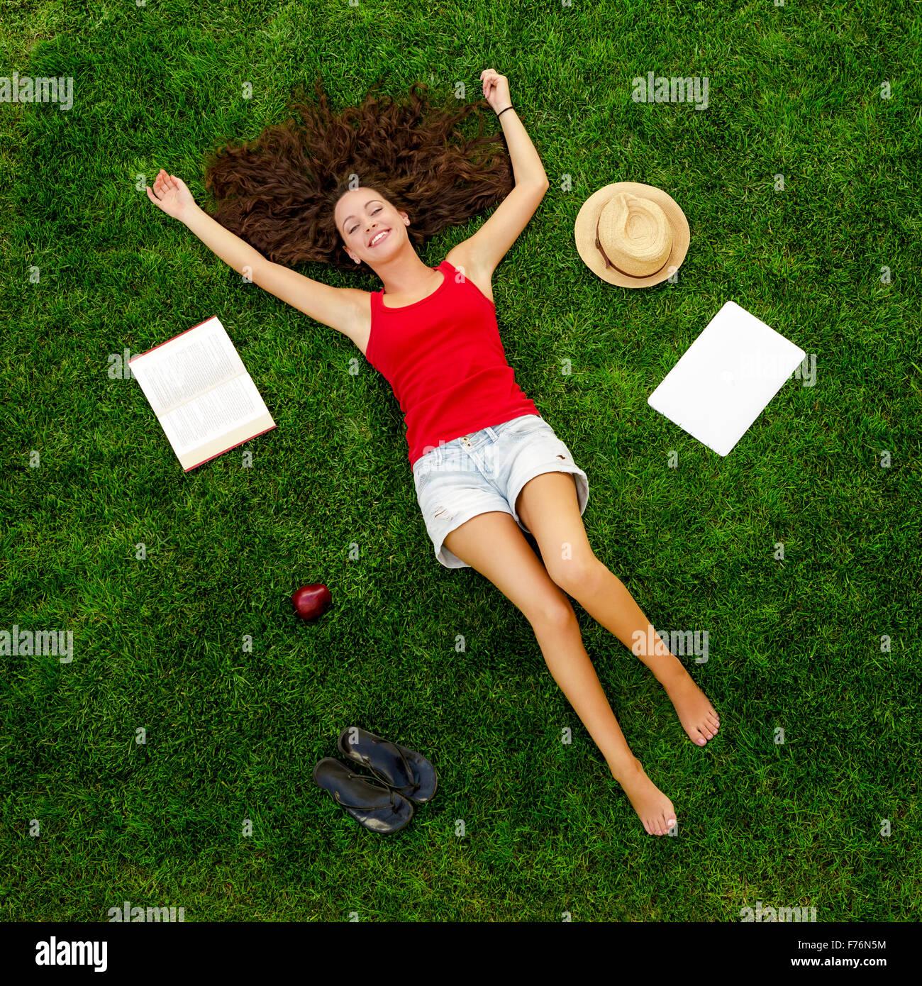 Schöne und glückliche junge Frau liegt auf dem Rasen Stockbild