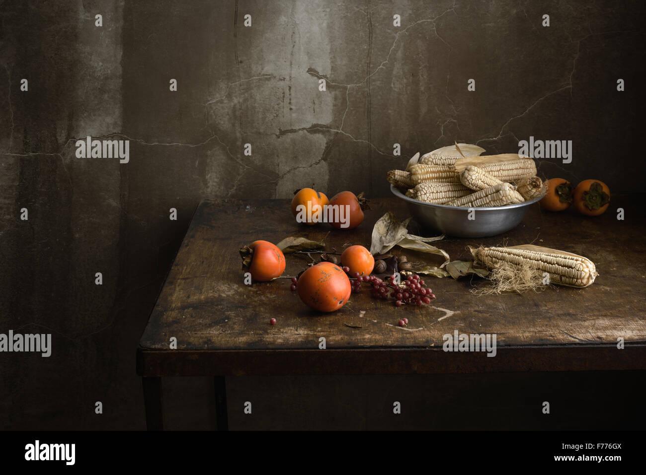 Stillleben mit Obst und Mais in einer Aluminiumschale auf einem alten Holztisch Stockbild