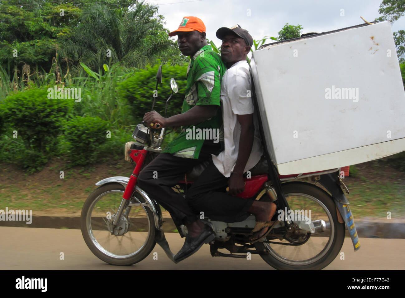 Zwei Freunde auf einem Motorrad transportieren einen Kühlschrank ...