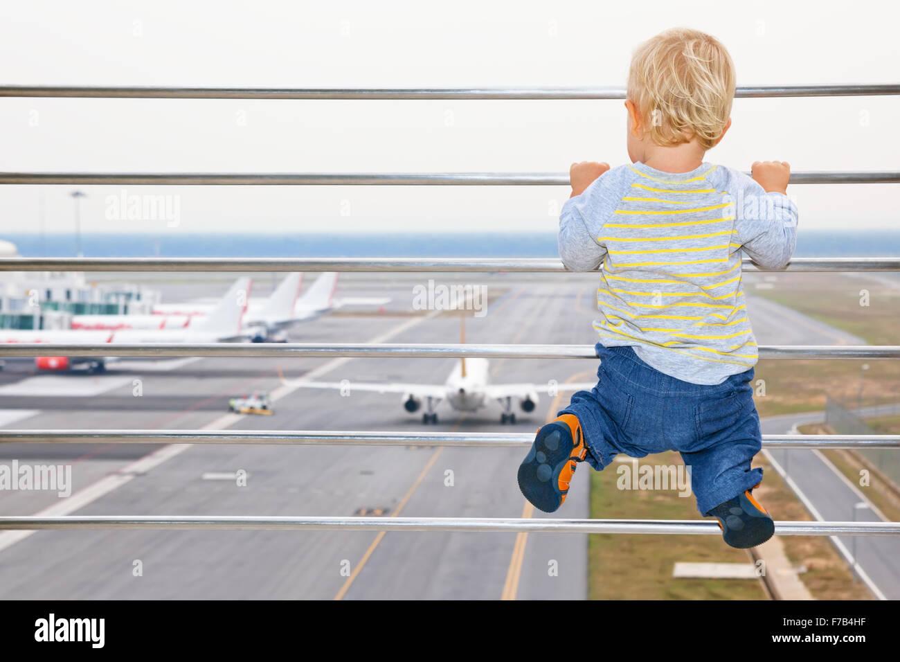Kleinen Jungen warten auf boarding, Flug im Flughafen-Transit-Halle und Blick auf Flugzeug in der Nähe von Stockbild