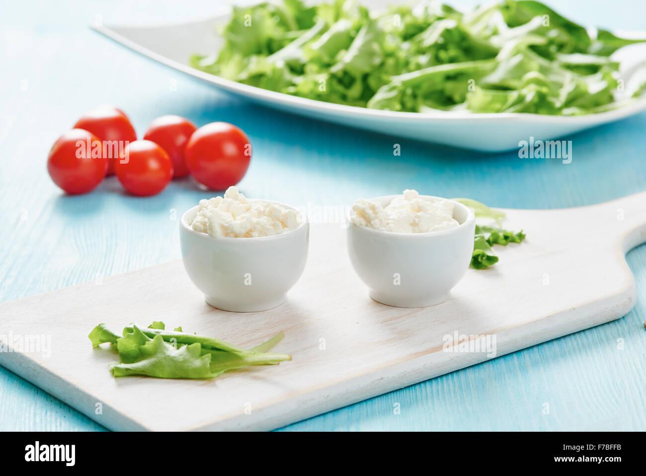 Hüttenkäse in zwei weißen Schalen auf blauen Holztisch, Salat und Tomate Stockfoto