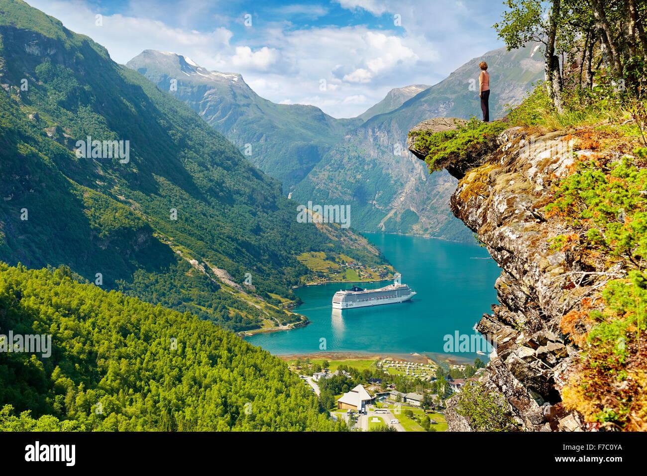 Touristen, die auf den Felsen stehen Kreuzfahrtschiff in Geiranger Fjord im Hintergrund, Norwegen Stockbild