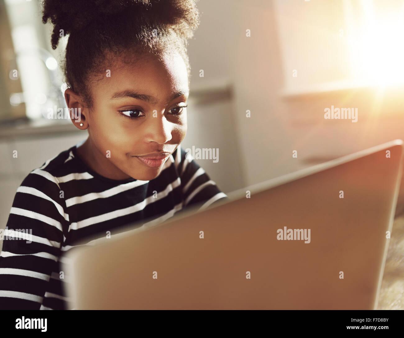 Lächelnd schwarze Mädchen mit einem Laptop zu Hause sitzen Lesen der Informationen auf dem Bildschirm Stockbild