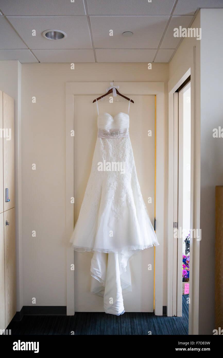 Weißes Brautkleid hängt an einem Türrahmen in einem Hotel vor einer ...