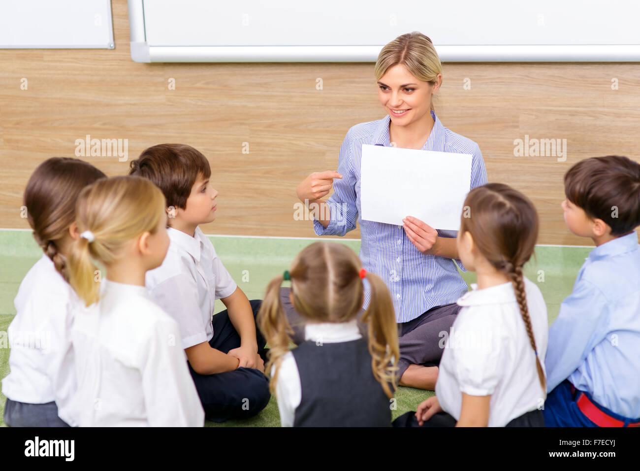 Lehrer und Kinder sitzen im Kreis zusammen. Stockbild