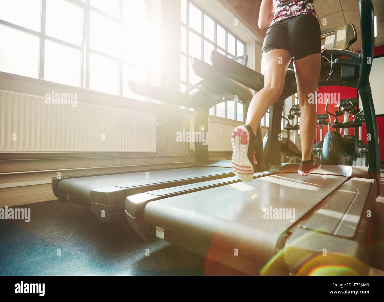 Rückansicht der Frau in Aktion auf Laufband. Konzentrieren Sie sich auf Frau Beine auf Laufband im Fitnessstudio Stockbild