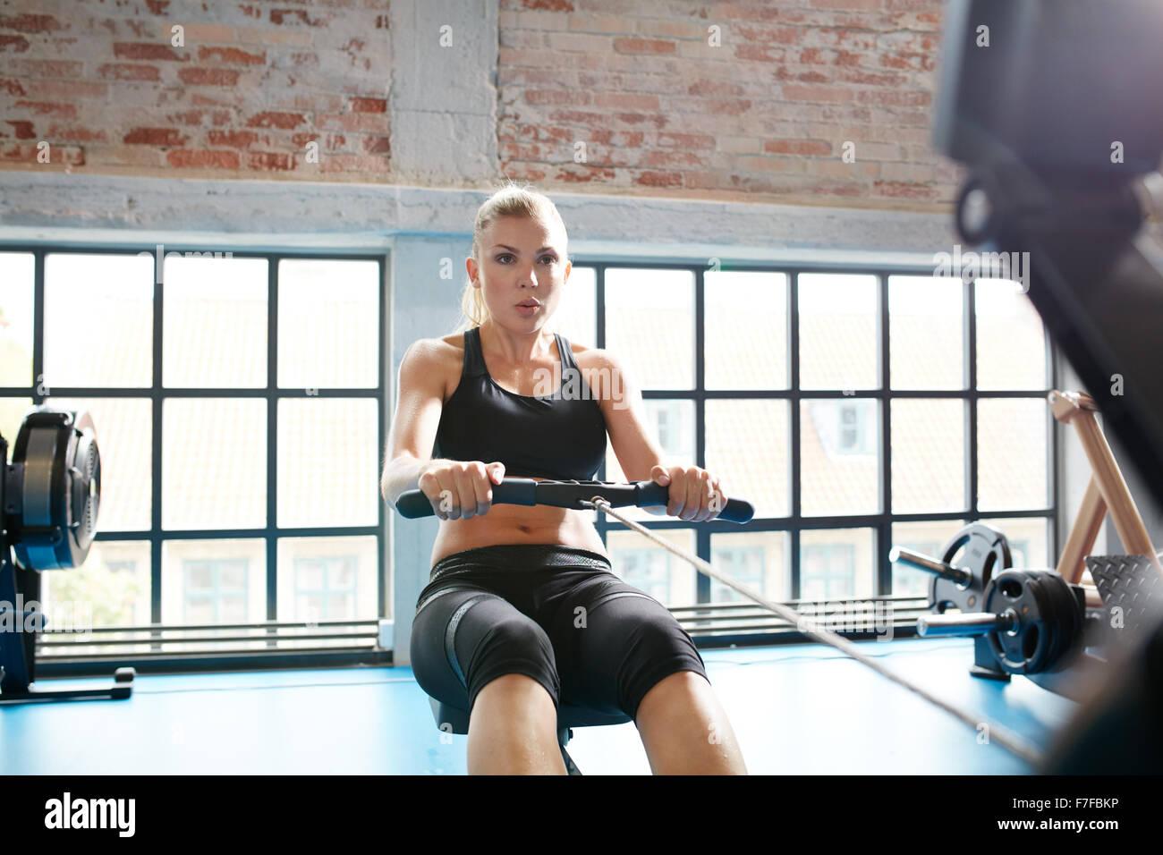 Kaukasische weiblich mit Rudergerät in der Turnhalle. Junge Frau Cardio-Training im Fitness-Club zu tun. Stockbild