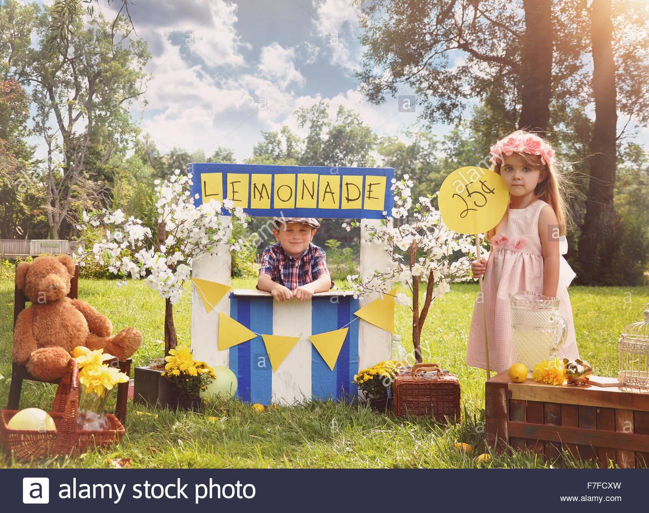 Zwei kleine Kinder verkaufen Limonade auf eine hausgemachte Limonadenstand an einem sonnigen Tag mit einem Preis Stockbild