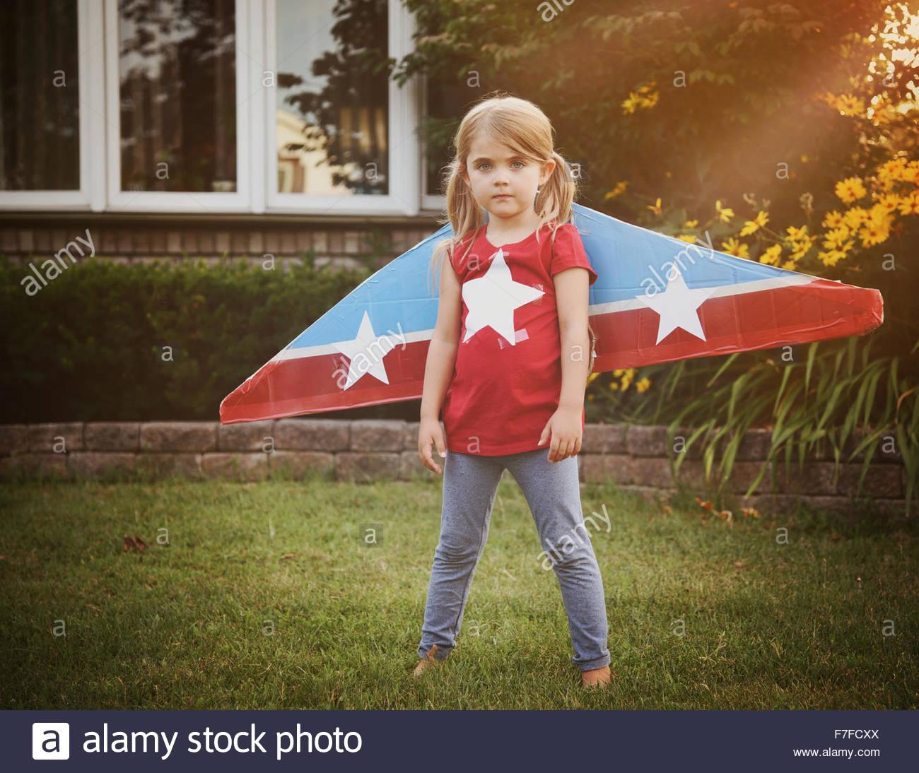 Ein kleines Kind trägt hausgemachten Karton fliegenden Flügel mit Sternen drauf, die vorgibt, ein Pilotprojekt Stockbild