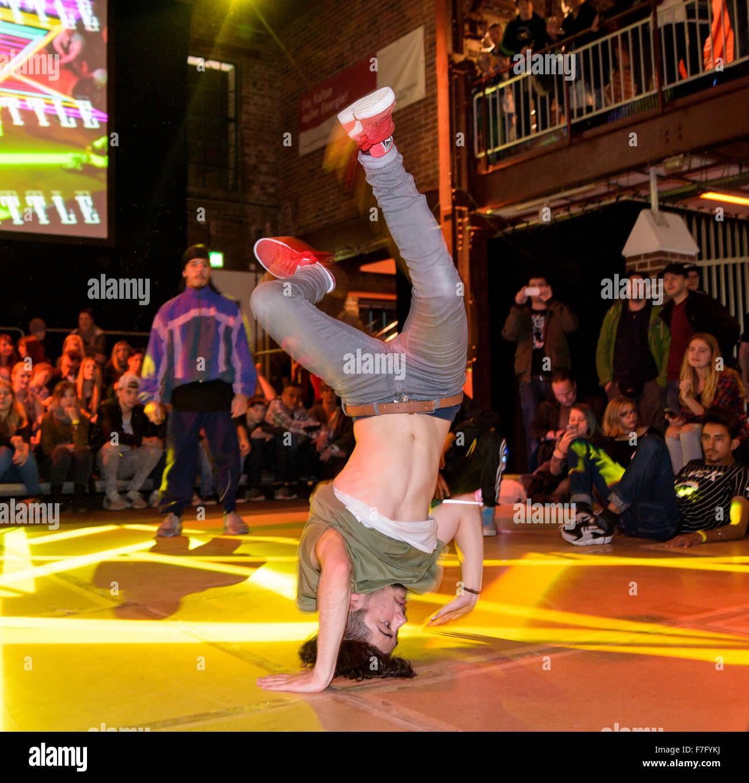 Ein junger Pause Tänzer führt auf einer Bühne in einem Breakdance-Wettbewerb. Stockbild