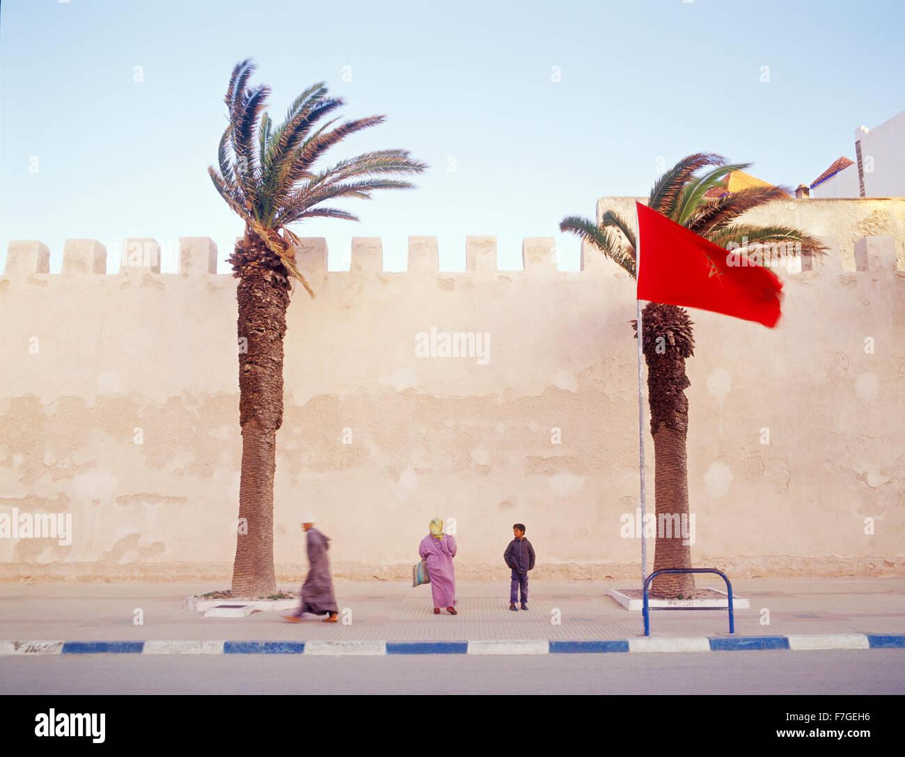 Ein marokkanischer Muslim geht zügig vorbei an der Stadtmauer auf seinem Weg zum Morgengebet. Essaouira, Marokko Stockbild