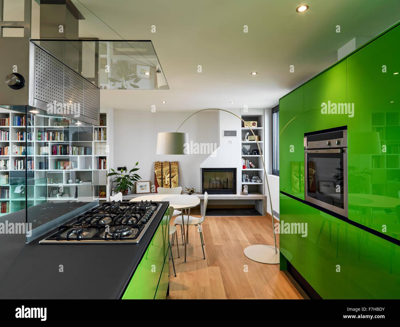 Grüne Küche mit Kochinsel in der Dachkammer mit Holzboden und Kamin ...