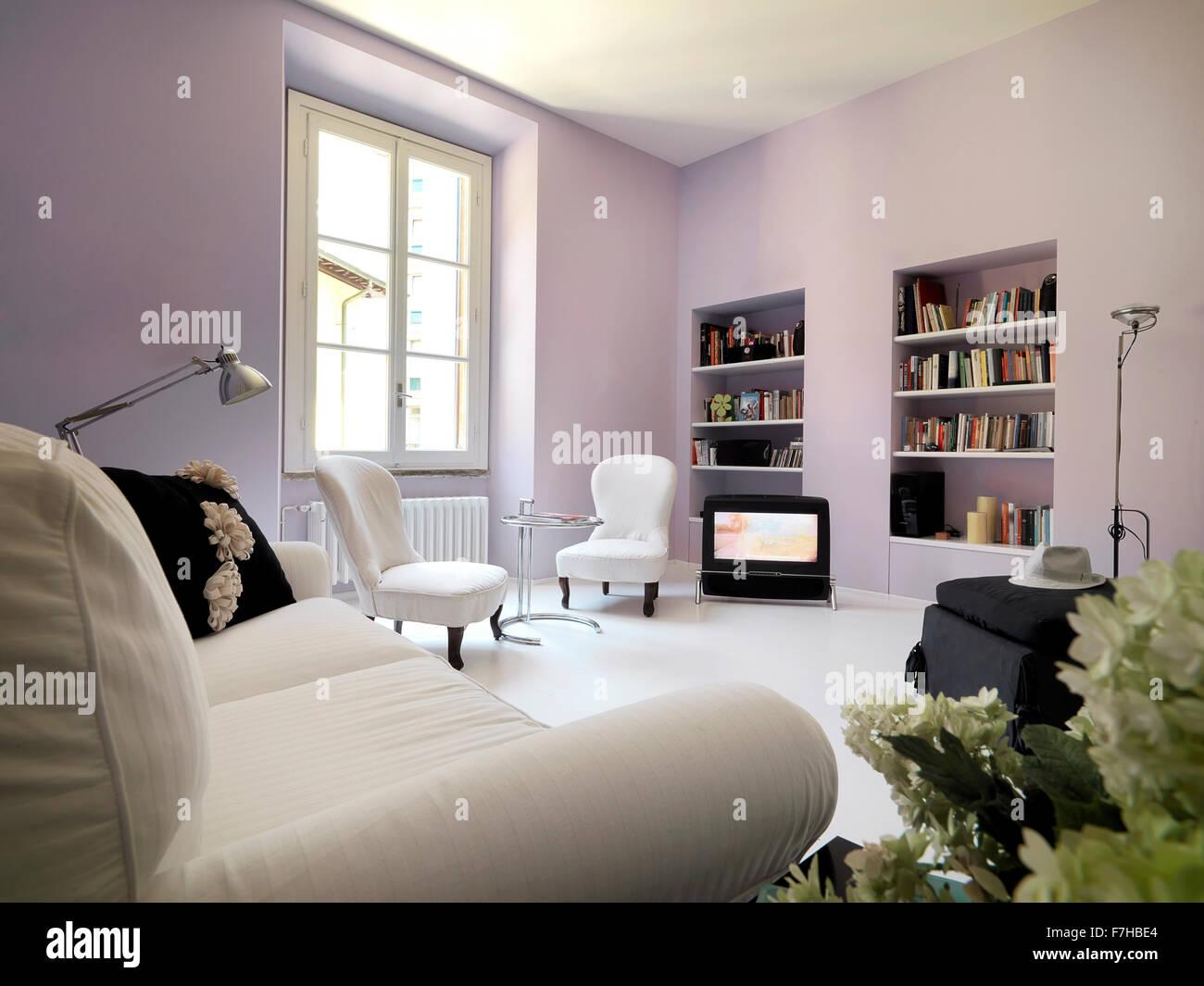 Klassische Wohnzimmer mit Wänden aus lila Farbe und Bücherregal Stockbild