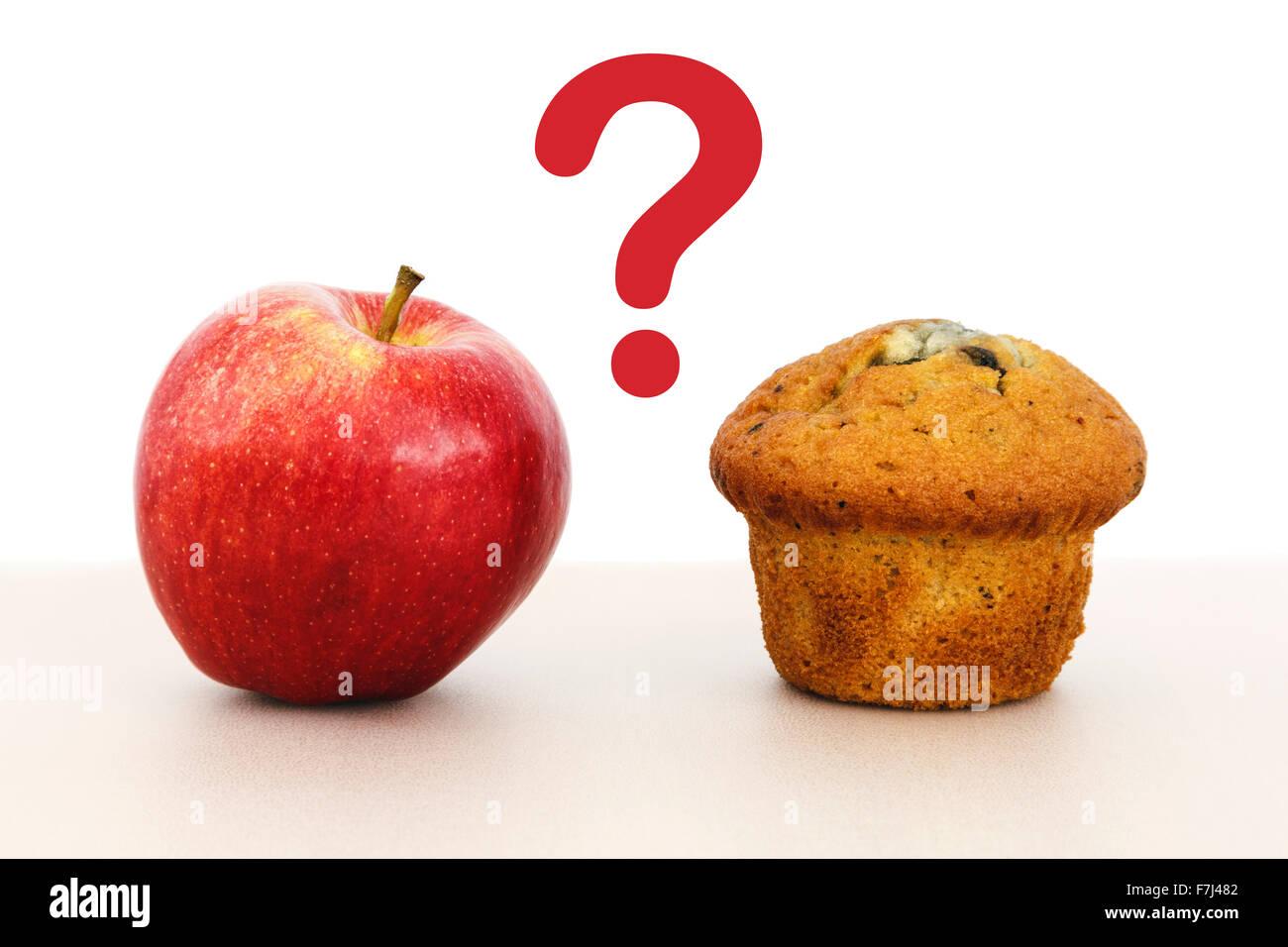 Rosy Red Apple und einen Muffin Kuchen auf einer Tischplatte mit einem Fragezeichen zwischen gesunden und ungesunden Stockbild