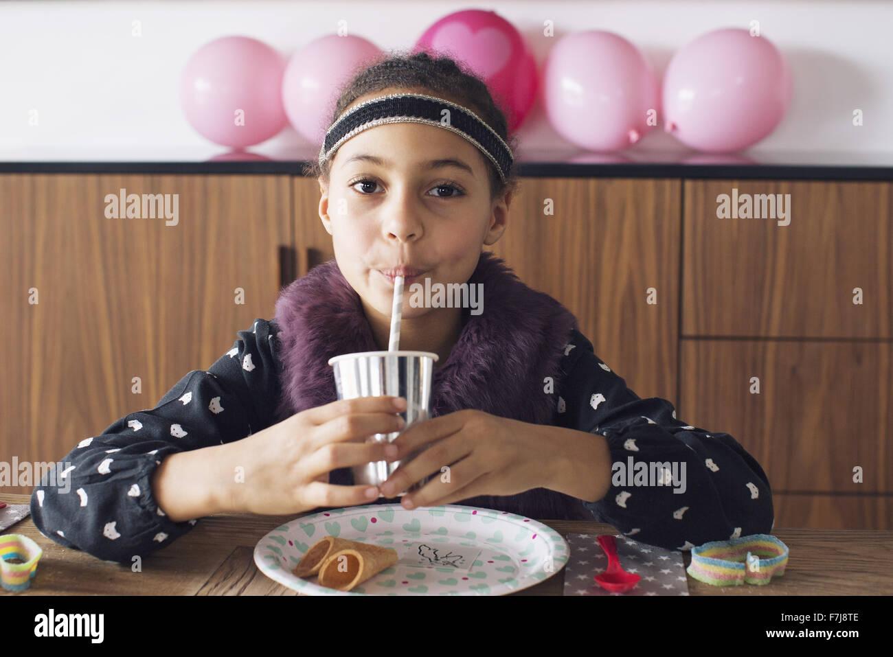 Mädchen trinken mit einem Strohhalm Stockbild